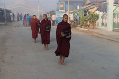 Young monks get food offerings in early morning Royalty Free Stock Images