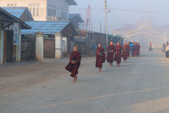 Young monks get food offerings in early morning Stock Photo