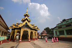 Young monks in pink robe with things on the head walking into a temple at Shwemawdaw Pagoda Stock Photos