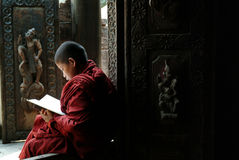 Young monks reading a book at Shwenandaw Monastery. Stock Photo