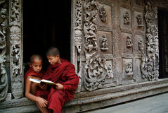 Young monks reading a book at Shwenandaw Monastery. Royalty Free Stock Photo