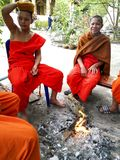 Young monks resting by the fire in the temple,luangprabang,laos. Young monks resting by the fire in the temple is taken in luangprabang,laos Royalty Free Stock Photos