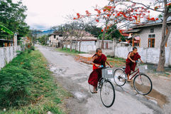 2 young monks riding bikes in Nyaungshwe. 2 young monks riding bikes in Nyaungshwe, Myanmar Stock Image