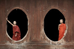 Inle Lake Myanmar, young monks at a Buddhist monastery standing in oval windows. Young novice Buddhist monks dressed in robes standing in wooden oval windows at Stock Photography