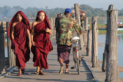 Young monks on U-Bein wooden bridge stock photos
