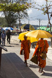 Young monks with umbrellas walking under the sun Stock Photo