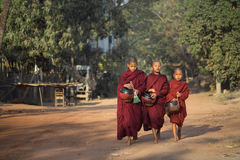 Young monks walk along road to collect alms Stock Photos