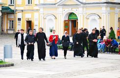 Young monks walk in Trinity Sergius Lavra along with visitors. Royalty Free Stock Photo