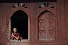Young monks at window of Nyan Shwe Kgua temple. Royalty Free Stock Photos
