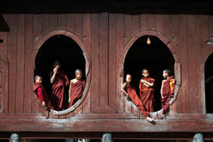 Young monks at window of wooden Church in temple. Stock Photo