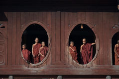 Young monks at window of wooden Church in temple. Stock Photos