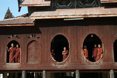 Young monks at window of wooden Church in temple. Royalty Free Stock Photography