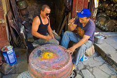Young moroccan men forging a copper pot Royalty Free Stock Photo