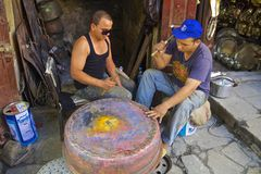 Young moroccan men forging a copper pot Royalty Free Stock Photography