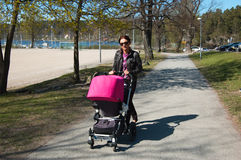 Young mother. Walking with pram Stock Image