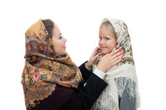 Young mother adjusts her shawl on the head daughter Stock Photo
