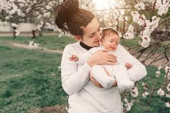 Young mother with adorable daughter in park with blossom tree. Happy mother and child stock photo