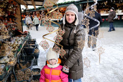 Young mother with amaze small daughter. On christmas market in Europe stock photography