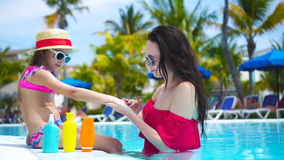 Young mother applying sun cream to kid hand outdoors. Sun protection and ultraviolet protection stock footage