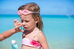 Young mother applying sunblock cream on her Stock Photo