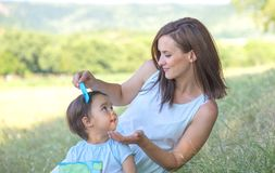 Young mother arranging her daughter`s hair royalty free stock image