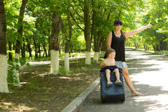 Young mother asking for a lift by the roadside Royalty Free Stock Images