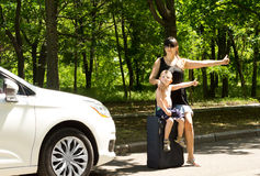 Young mother asking for a lift by the roadside Royalty Free Stock Image