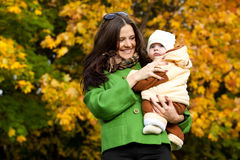 Young mother with baby in arms up. In fall city park Stock Image