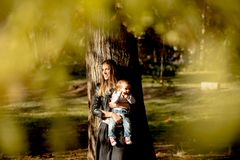 Young mother and baby boy in autumn park Stock Photos
