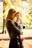 Young mother and baby boy in autumn park royalty free stock image