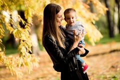 Young mother and baby boy in autumn park royalty free stock photo
