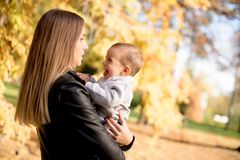 Young mother and baby boy in autumn park stock photography