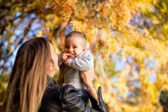 Young mother and baby boy in autumn park royalty free stock images