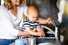 Young mother with a baby boy doing housework. Unrecogniozable young mother with a baby son doing housework. Beautiful women and baby boy washing up the dishes Royalty Free Stock Image