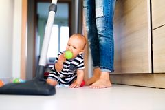 Young mother with a baby boy doing housework. Royalty Free Stock Images