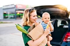 Young mother with baby boy in front of a supermarket. Beautiful young mother with her little baby son in front of a supermarket, holding paper shopping bag Stock Image