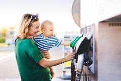 Young mother with baby boy at the petrol station. Young mother with baby boy at the petrol station going to refuel the car Royalty Free Stock Photography