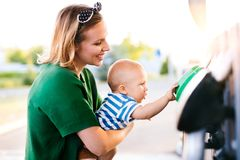 Young mother with baby boy at the petrol station. Royalty Free Stock Photography