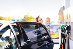 Young mother with baby boy at the petrol station. Young mother with baby boy at the petrol station going to refuel the car royalty free stock photo