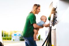 Young mother with baby boy at the petrol station. Stock Photos