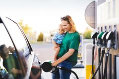 Young mother with baby boy at the petrol station. Young mother with baby boy at the petrol station refuelling the car Royalty Free Stock Image