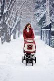 Young mother with baby carriage. In winter forest Royalty Free Stock Images
