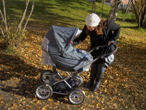 Young mother with baby carriage. Young mother is out in the fresh autumn air with her baby carriage Stock Photo