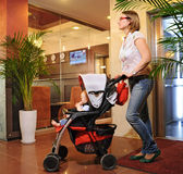 Young mother with a baby carriage rolls in the house. Young mother with a baby carriage rolls in the lobby of the house Royalty Free Stock Images