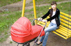 Young mother with a baby carriage on a swing Royalty Free Stock Photography