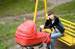 Young mother with a baby carriage on a swing Royalty Free Stock Photos
