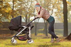 Young mother with a baby carriage walking in a park. A young mother with a baby carriage walking in a park Stock Photos