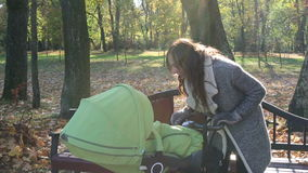 A young mother with a baby carriage walking in a park. Beautiful woman with long hair standing outdoors with a stroller. Beautiful autumn. Sun rays penetrate stock footage