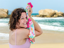 Young mother and Baby Cloth in the Beach. A young mother exhibiting the cloth of her baby in the beach Stock Images