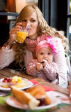 Young mother and baby daughter having breakfast Stock Photography